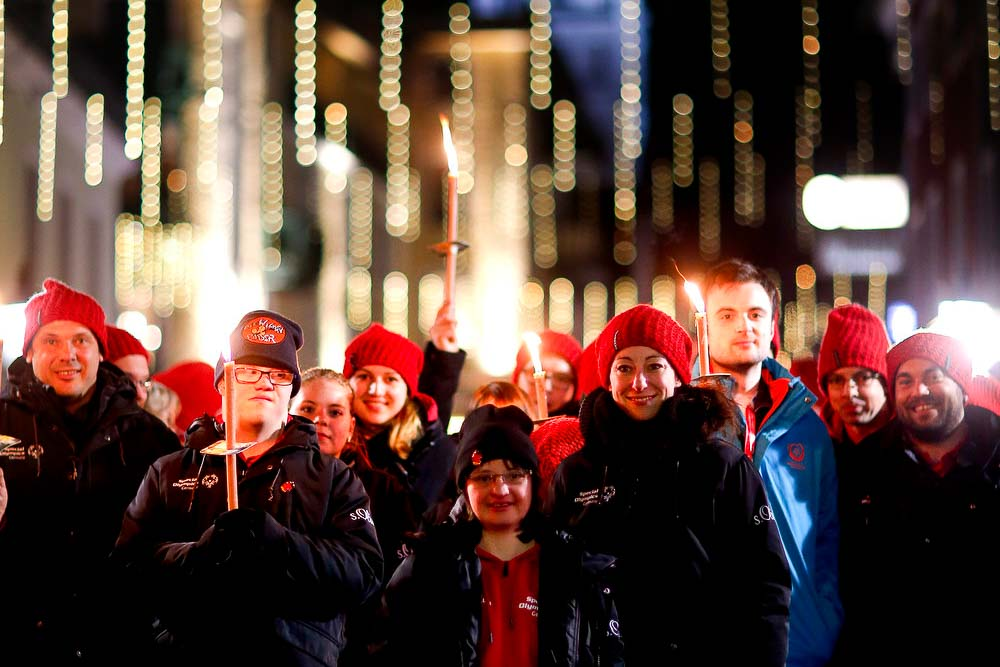 People in heavy coats hold candles as a group at night.