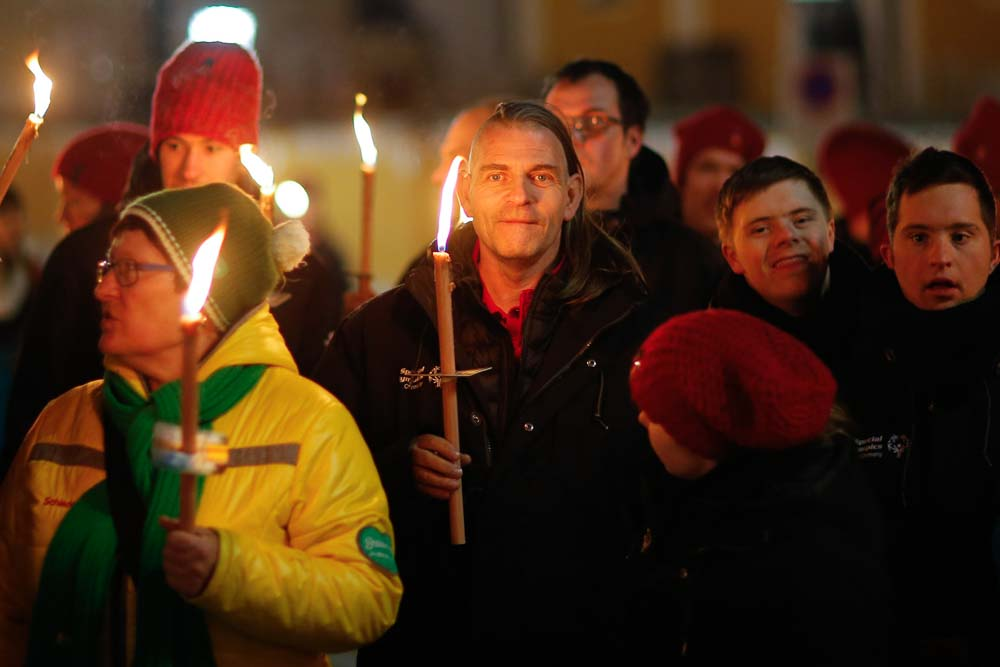 Closeup photo of several people holding brightly burning candles.