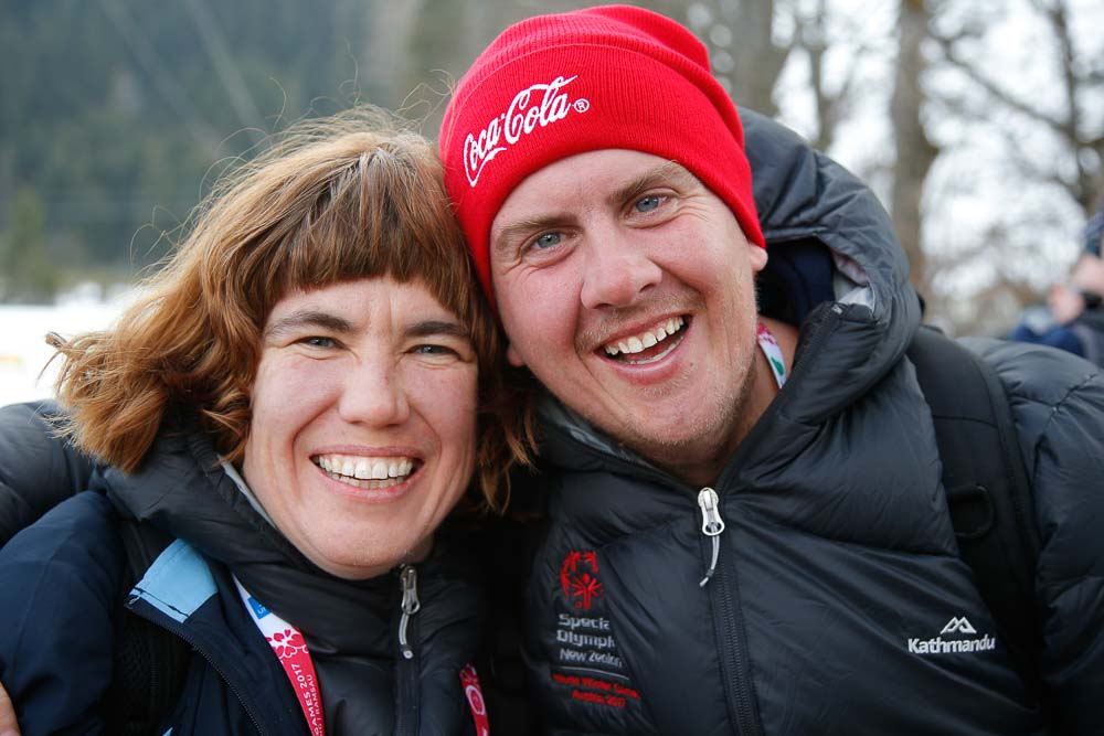 A man and a women in winter coats pose smiling.