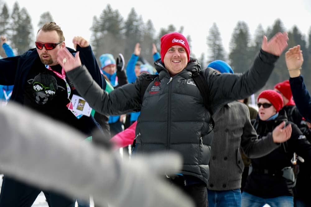 People in coats lift their arms as they exercise.