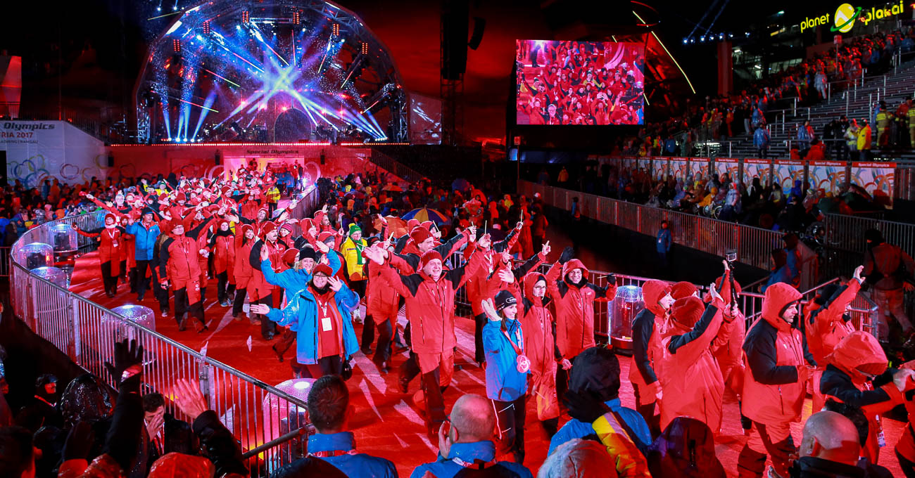 A stream of people in bright clothing walk from a big stage along a raised path.