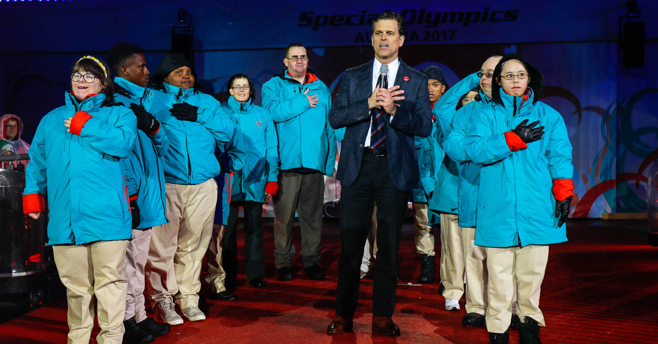 Tim Shriver stands in front of a group of nine other people on stage.
