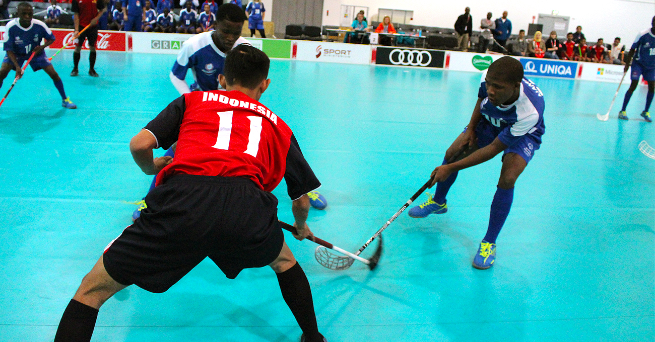 three Atlhetes going after the ball and the one in red defending the goal