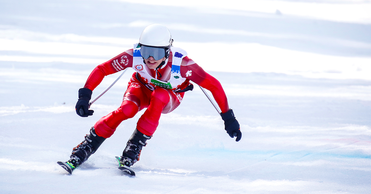 Male apline skier races toward the finish line.