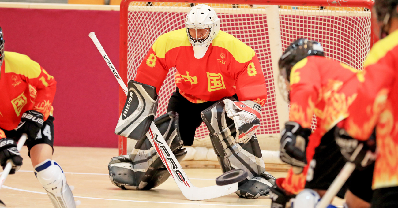 A floor hockey goalie defends a strong shot taken by the opposing team.