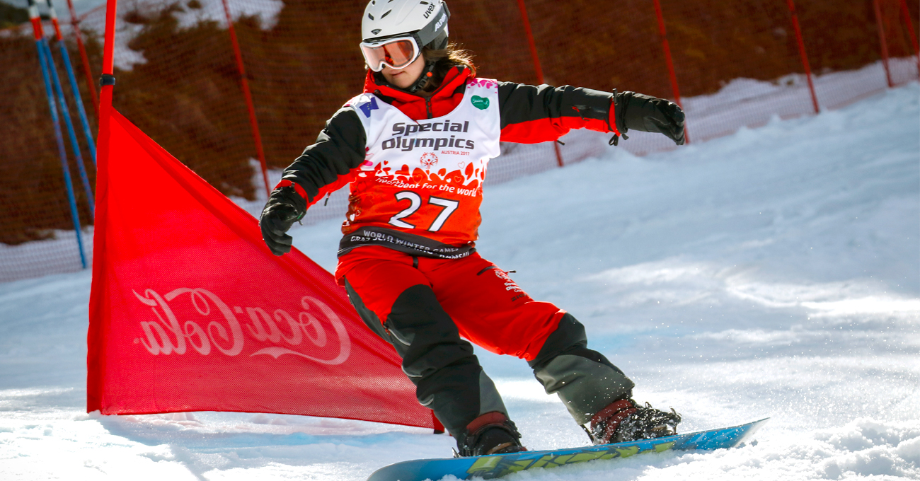 Female Snowboarder weaves between flags down the slopes during competition.