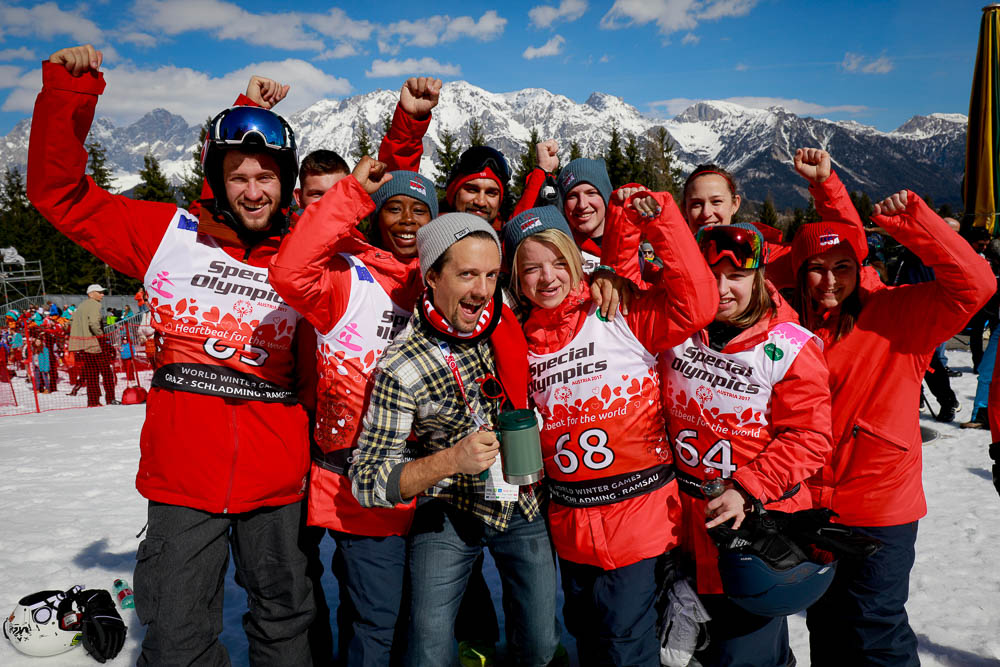 Singer Jason Mraz in a flannel shirt poses with skiers in red jackets.