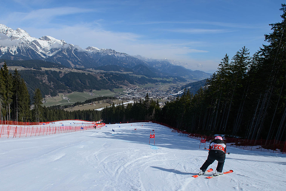 A landscape view with snowcapped mountains in the distance and a crouching skier about to start a ski run.